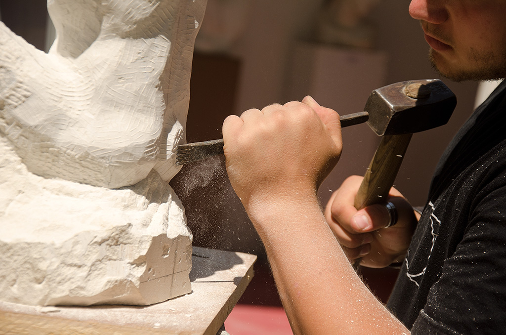 Chiselling away stone from a sculpture
