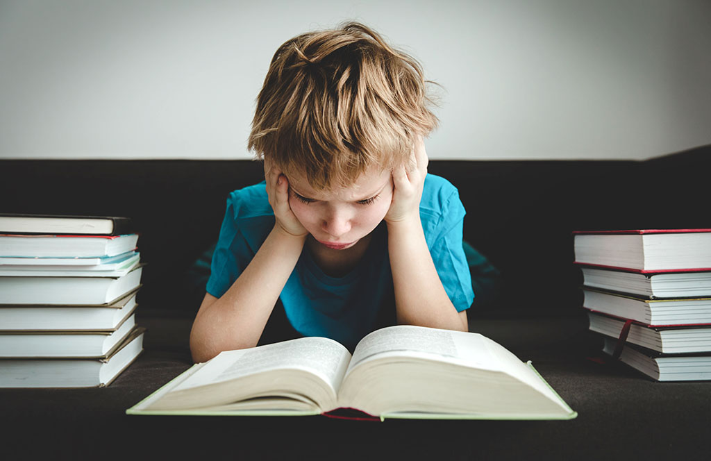 Little boy puzzled at meaning of book
