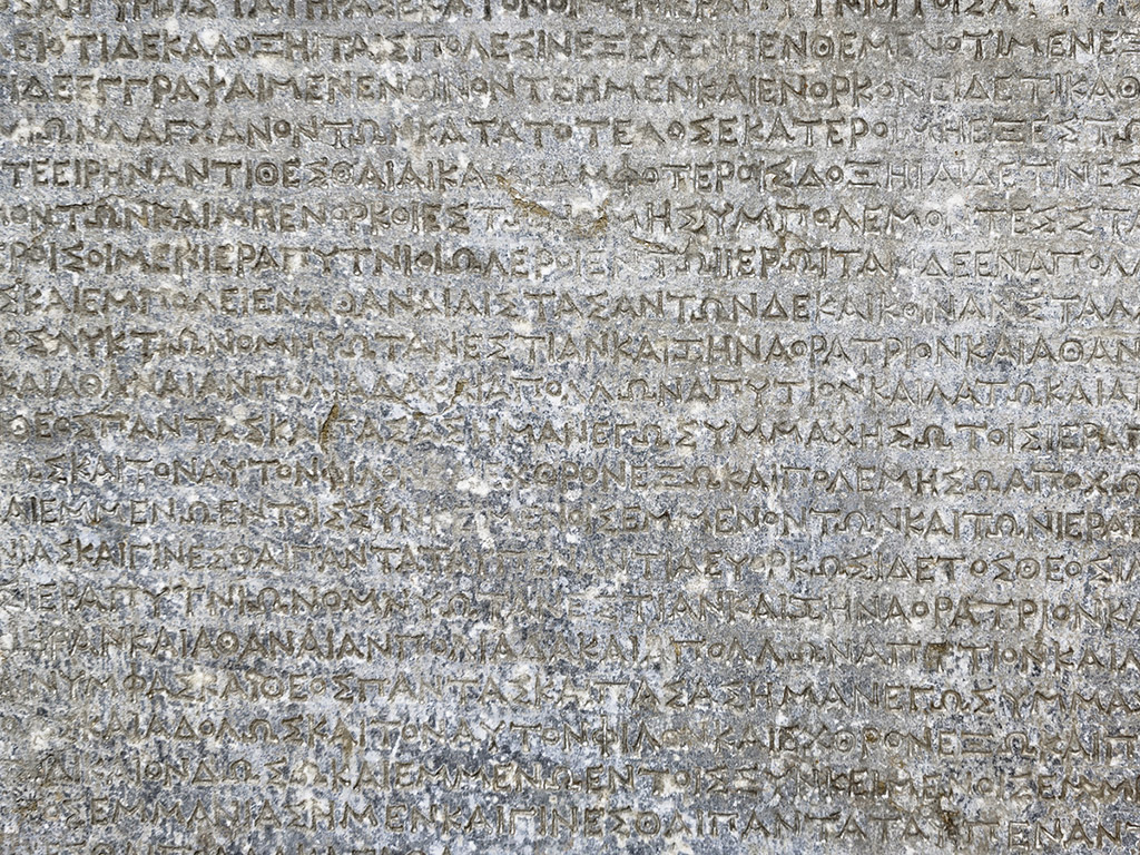 Greek letters carved on grey stone wall